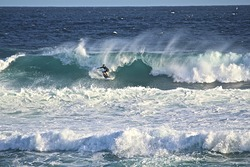Surfer taking on Soldiers point, Soldiers Beach photo