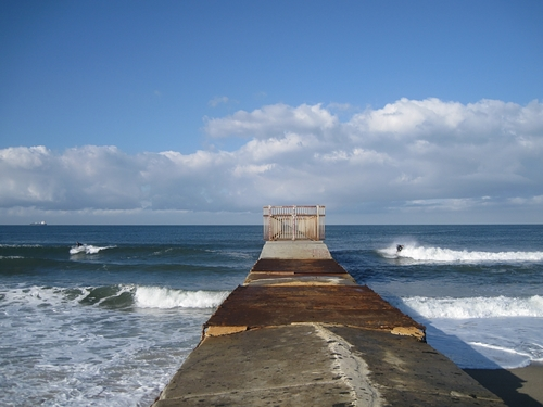 Surfers on each side of groyne, Gillis
