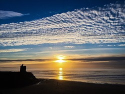 Sunset, high clouds, silhouetted Green Castle, Ballybunion photo